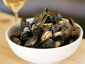 Bowl of mussels with glass of white wine